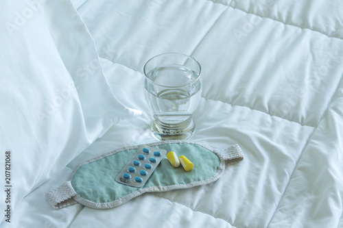 Fotografia  Blister pack of sleeping pills, blindfold and glass of water