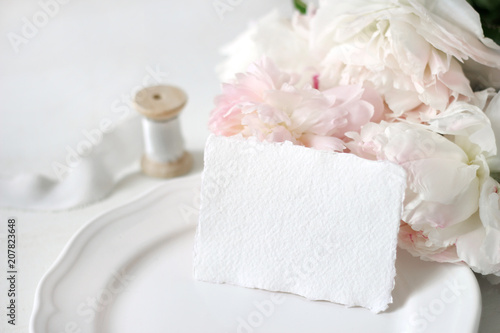 Bright wedding or birthday stationery mockup scene with a handmade paper greeting card, porcelain plate, spool of silk ribbon and pink peony flowers a white table background. Feminine styled stock