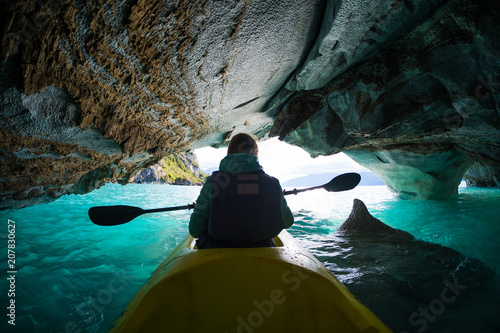 Photo Woman with kayak explores the Marble Caves, paddles inside the cave with interesting patterns on the walls and crystal clear water