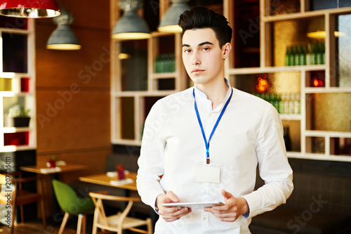 Obraz na plátne Confident young man wearing white shirt and Id card standing with tablet in coffee break room and looking at camera