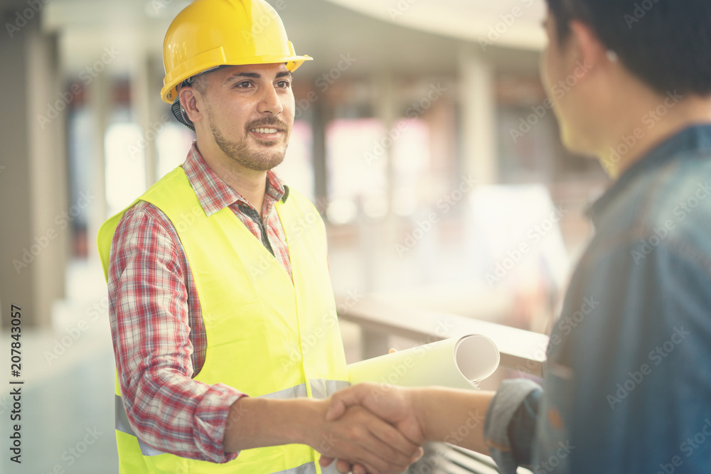 Fototapeta Engineer worker shaking hand with customer or co worker in the office