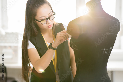Waist up portrait of focused Asian woman working in fashion design tracing sewing dummy standing at tailors table in sunlit modern atelier studio, lens flare