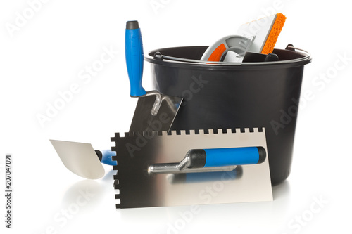 Photo  Masonry tools - trowels, notched trowel and mortar bucket - on white