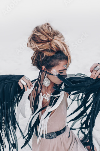 beautiful young fashionable boho style woman sitting on the beach at sunset Wall mural
