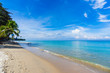 Tropical beach with coconut trees and blue sky in Koh Lanta island, Thailand.