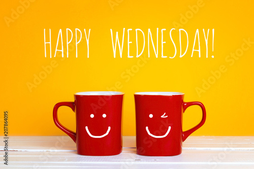 Two red coffee mugs with a smiling faces on a yellow background  with the phrase Happy wednesday.