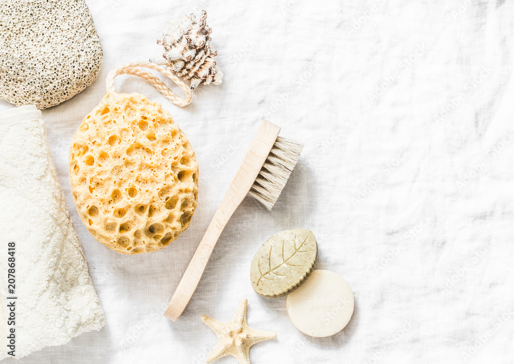 Fototapeta Shower accessories - face brush, sponge, pumice stone, towel, soap on a light background, top view. Cleansing of the skin health concept. Flat lay