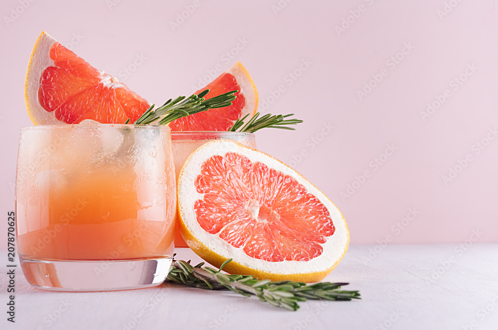 Fotografie, Obraz Cold grapefruit cocktail with ice, rosemary and pieces grapefruit on pastel pink background, closeup
