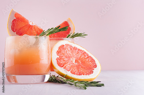 Cold grapefruit cocktail with ice, rosemary and pieces grapefruit on pastel pink background, closeup. Fresh summer healthy diet beverage.