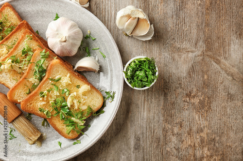 Foto op Plexiglas Aromatische Plate with delicious homemade garlic bread on table