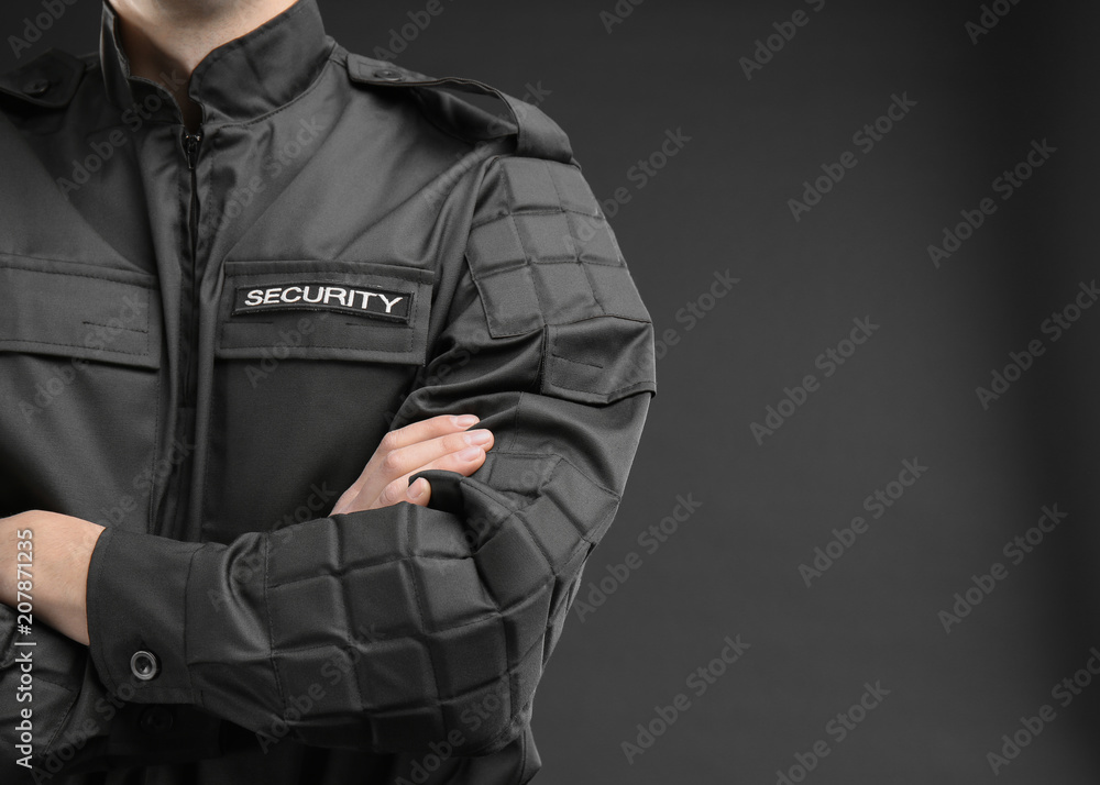 Fototapeta Male security guard in uniform on dark background, closeup