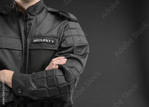 Foto  Male security guard in uniform on dark background, closeup