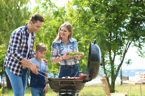 Happy family having barbecue with modern grill outdoors Canvas Print