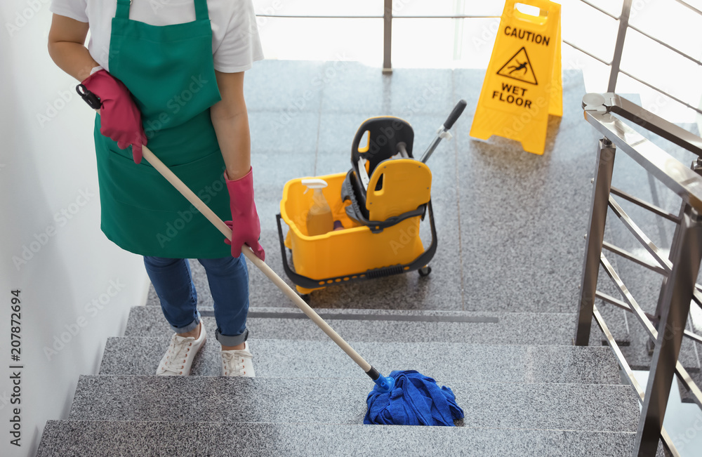 Fototapety, obrazy: Young woman with mop cleaning stairs