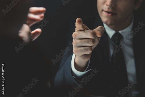 Angry man in formal business suit pointing hand to somesone he talking to in dar Canvas Print