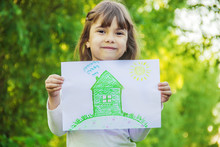 Drawing Of A Green House In The Hands Of A Child. Selective Focus.
