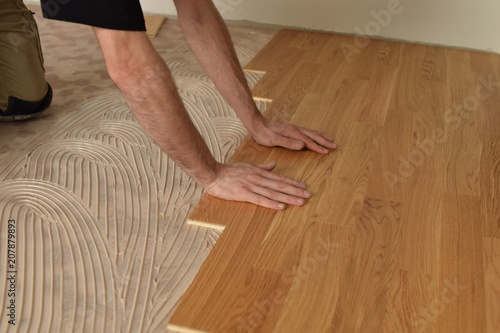 Fototapeta close up of worker installing wood parquet obraz na płótnie