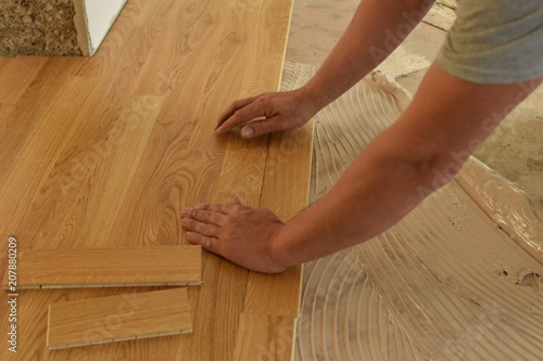 Obraz close up of worker installing wood parquet - fototapety do salonu