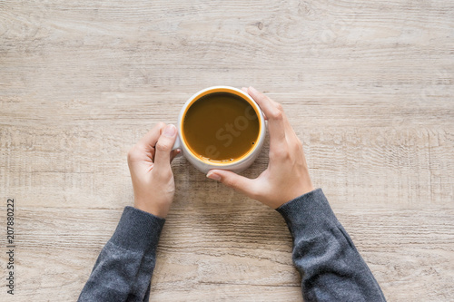 Foto op Plexiglas Chocolade Female hand holding cup of coffee on wood texture background.