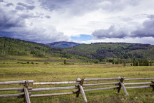 Clouds Hang Over The Rocky Mountains With A Wood Fence Built Across A Green Meadow In The Foreground In Colorado, USA