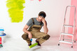 tired young man sitting with paint roller near ladder in front of painted wall