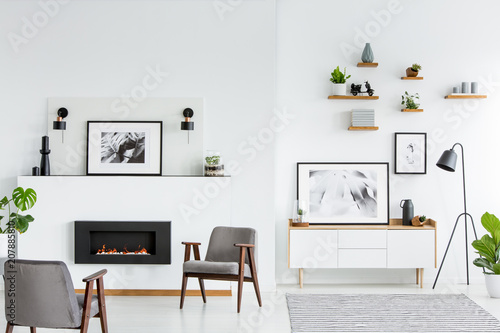 Papiers peints Individuel Grey armchairs in white spacious living room interior with posters and fireplace. Real photo