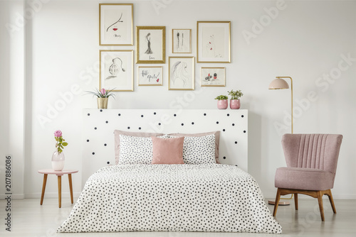 Fotografía  Feminine bedroom interior with a double bed with dotted sheets, armchair, art co