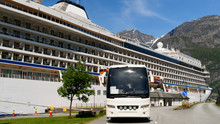 Tourist Bus Parked In Front Of A Cruise Ship In Eidfjord, Norway, On A Sunny Day. Lovely Mountain Landscape Behind The Ship. Logos And Id Removed.