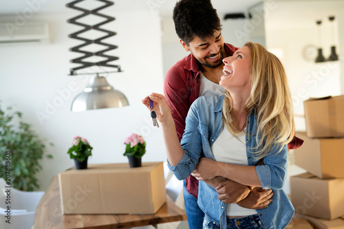 Valokuva  Young couple unpacking cardboard boxes at new home moving in concept