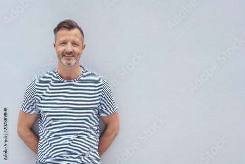 Photographie  Friendly middle-aged man posing against a wall