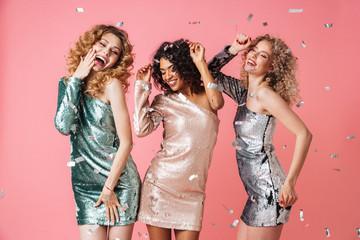 Three beautiful laughing women in shiny dresses