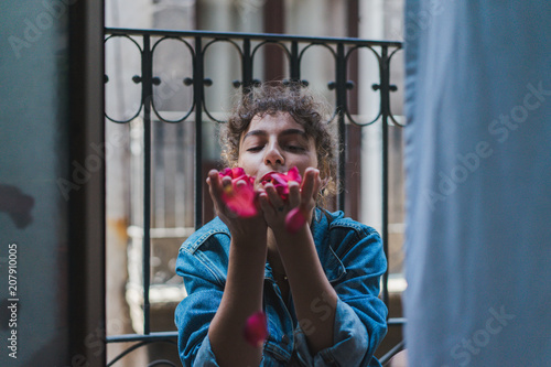 Laughing woman blowing tender petals away