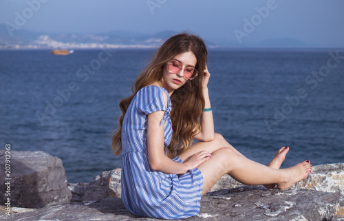 Fotografía  Pretty sad serious girl in pink sunglasses sitting on the stones near sea