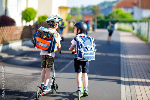 Photographie  Two school kid boys in safety helmet riding with scooter in the city with backpack on sunny day