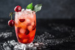 Fresh cherry cocktail. Fresh summer cocktail with cherry and ice cubes. Glass of cherry soda drink on dark stone background.
