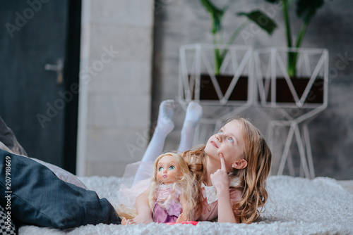 Tela little daughter playing mother with doll
