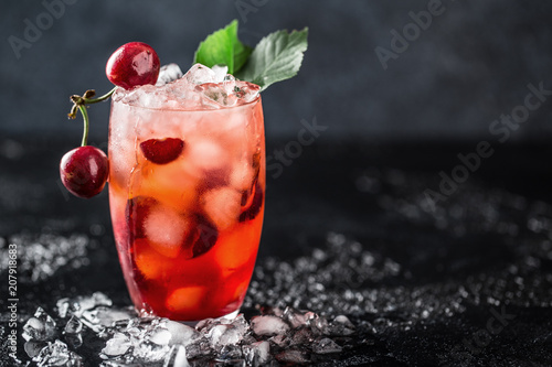 Papiers peints Cocktail Fresh cherry cocktail. Fresh summer cocktail with cherry and ice cubes. Glass of cherry soda drink on dark stone background.