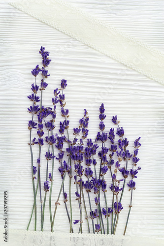 Small flowers of lavender with lace braid on white wood background with copy space. Top view. Provans style photography.