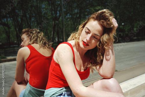 Fotografía  Atractiva mujer rubia posando junto a una pared de espejo en un día de verano