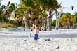 Adorable active little kid boy having fun on Miami beach, Key Biscayne. Happy cute child feeding seagull birds on sunny warm day near palms