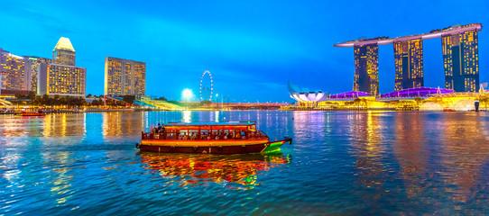Panorama singapurskih zgrada, nebodera i ferris kotača koji se ogledaju u moru. Turistički brod plovi uvarom navečer. Singapurski obzor u plavom satu. Zaljev marine na rivi noćnog prizora.