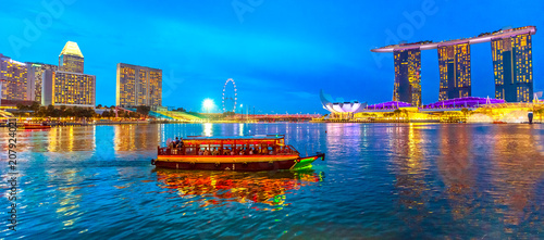 Panorama of Singapore buildings, skyscrapers and ferris wheel reflected in the sea. Tourist boat sails in the bay at evening. Singapore skyline at blue hour. Night scene waterfront marina bay.