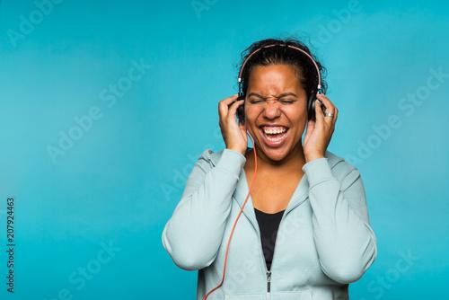 Foto  Junge attraktive Mischrassefrau, welche die Musik hört mit blauem Hintergrund de