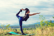 Young beautiful woman doing yoga exercises outdoors.