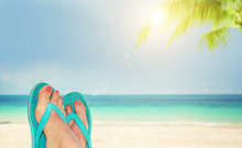 Woman Feet With Blue Flip Flops, Beach And Sea In The Background, Travel And Summer Concept