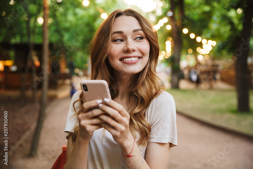 Obraz Satisfied young girl holding mobile phone while - fototapety do salonu