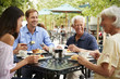 canvas print picture - Senior Parents With Adult Children Enjoying Meal At Outdoor Cafe