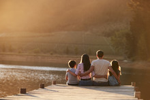 Rear View Of Family Standing On Wooden Jetty By Lake