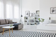 Table on patterned carpet in open space interior with white bed and grey corner sofa. Real photo