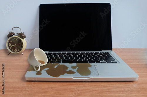 Fotografija  Coffee Cup spill out on Laptop Keyboard on wooden floor, Accident computer repair concept